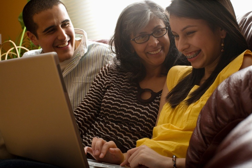 latino family laughing using laptop