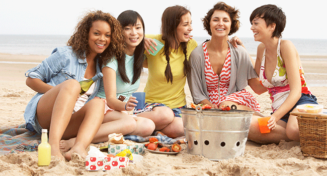 A group of female friends sitting on the beach discussing what their Palmdale, California dentist told them about wisdom teeth.